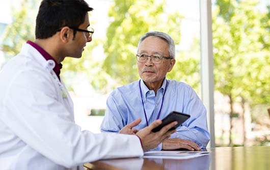 A male Proton therapy physician discussing proton therapy with an elderly male patient.