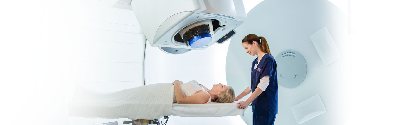 A female employee gets a female patient setup on a table for proton therapy.