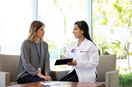 A female proton therapy physician discussing proton therapy with a young woman.